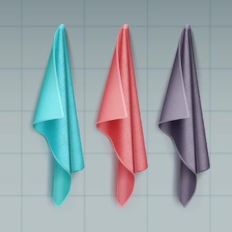 Ilustracja wiszące kolorowe ręczniki bawełniane lub frotte drapowane na białym tle na kafelkowej ścianie