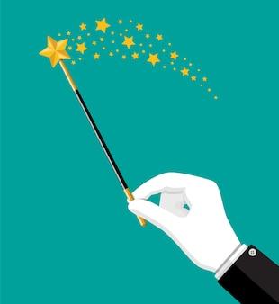 Iluzjonistyczny magiczny kij z blaskiem. różdżka cudownego czarodzieja w dłoni. cyrk, widowisko magiczne, komedia.