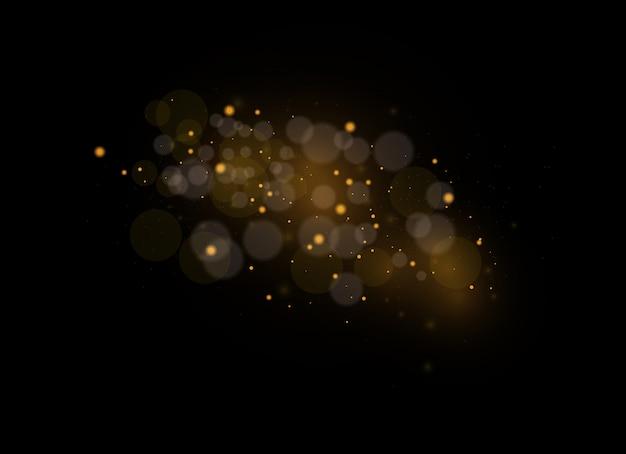 Iskry pyłu i złote gwiazdy świecą specjalnym światłem. lśniące magiczne cząsteczki pyłu.