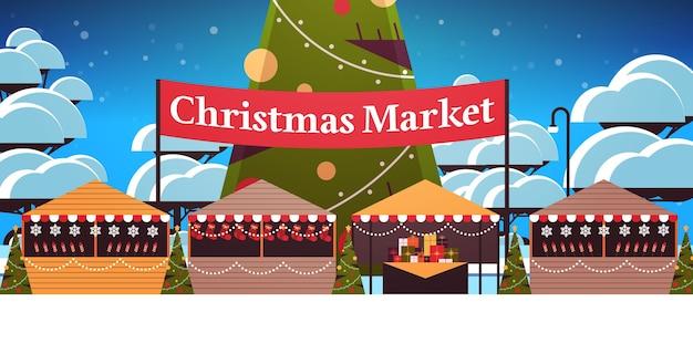 Jarmark bożonarodzeniowy lub świąteczny targ na świeżym powietrzu z dekorowaną jodłą wesołych świąt bożego narodzenia nowy rok ferie zimowe koncepcja tło krajobraz