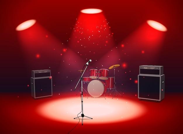 Jasna, pusta scena z mikrofonem, zestawem perkusyjnym i wzmacniaczami w świetle reflektorów