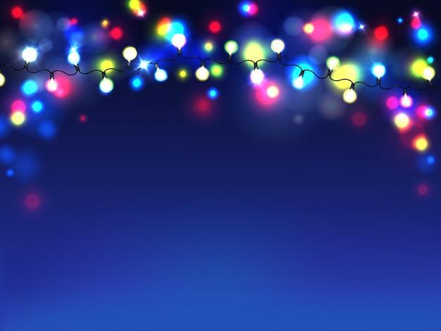 Jasne girlandy na białym tle na niebieskim tle. rozproszone światła żarówek elektrycznych