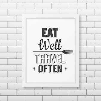 Jedz dobrze, często podróżuj - cytuj typograficzną realistyczną białą kwadratową ramkę na ścianie z cegły.