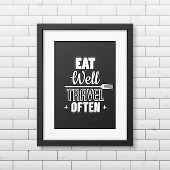 Jedz dobrze, często podróżuj - cytuj typograficzną realistyczną czarną ramkę na ścianie z cegły.