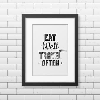 Jedz dobrze, często podróżuj - typograficzny cytat w realistycznej kwadratowej czarnej ramce na ścianie z cegły.