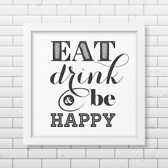 Jedz, pij i bądź szczęśliwy - cytuj typograficzną realistyczną kwadratową białą ramkę na ścianie z cegły.