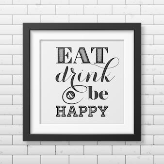 Jedz, pij i bądź szczęśliwy - typograficzny cytat w realistycznej kwadratowej czarnej ramce na ścianie z cegły.