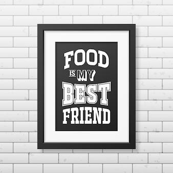 Jedzenie jest moim najlepszym przyjacielem - cytat typograficzny w realistycznej kwadratowej czarnej ramce na ścianie z cegły