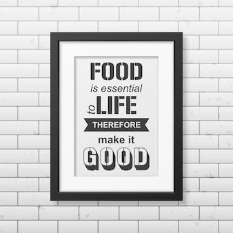 Jedzenie jest niezbędne do życia, więc czyń je dobrym - cytuj typografię w realistycznej kwadratowej czarnej ramce na ścianie z cegły
