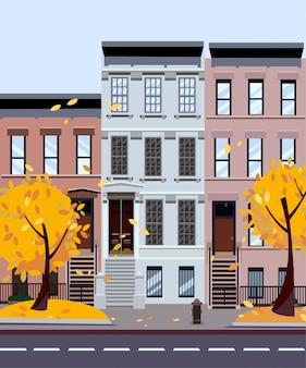 Jesienna ulica miasta. trzy-czteropiętrowe domy. uliczny pejzaż miejski. dzień krajobraz miasta z jesiennych drzew na pierwszym planie