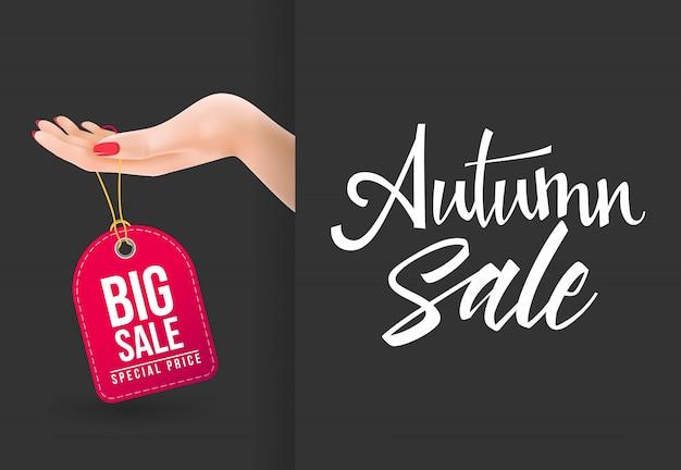 Jesienna wyprzedaż, duża sprzedaż napis z ręki trzymającej tag
