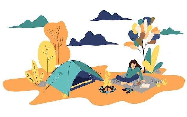 Jesienny kemping dziewczyna sama cieszy się rekreacją na świeżym powietrzu przy ognisku