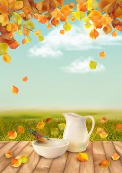Jesienny krajobraz z dzbanem i wodą pitną dla ptaków z ceramicznej miski