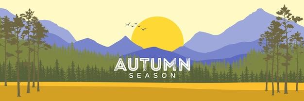 Jesienny krajobraz z żółtą łąką, lasem, górą i jeziorem na zachmurzonym niebie.