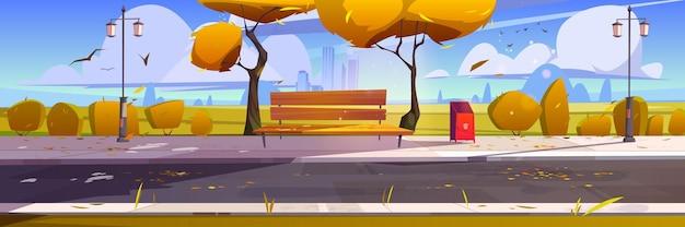 Jesienny park miejski z drewnianą ławką, żółtymi drzewami i opadłymi liśćmi