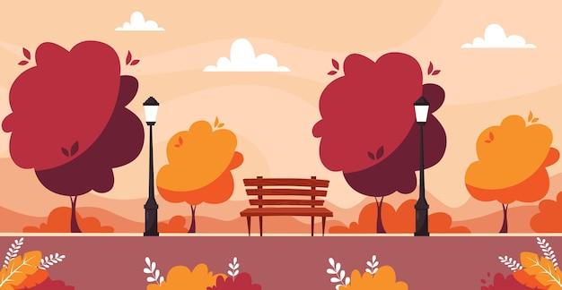 Jesienny park miejski z drzewami, krzewami, ławką, latarnią.