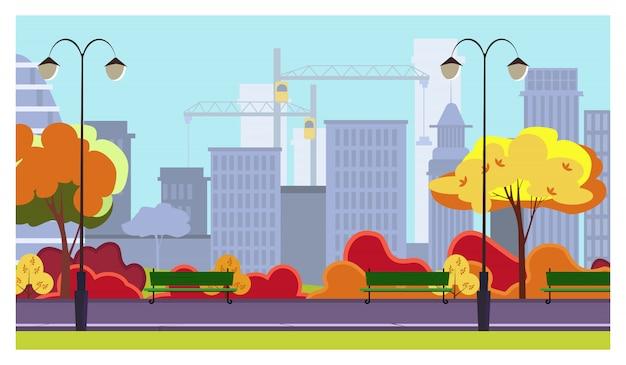 Jesienny park miejski z drzewami, krzewami, ławkami, latarniami