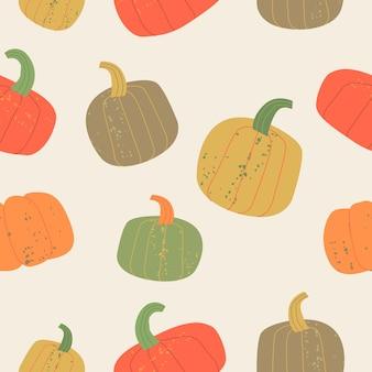 Jesienny wzór na beżowym tle ciepła kolorystyka kolorowe dojrzałe dynie
