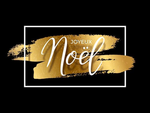 Joyeux noel tekst na złotych pociągnięciach pędzla i białej prostokątnej ramce na czarnym tle, francuskie święta.