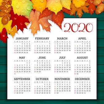 Kalendarz na rok 2020 z kolorowymi liśćmi na drewnianym wektorze