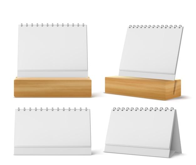 Kalendarze biurkowe z metalową spiralą i pustymi stronami na białym tle. realistyczny kalendarz papierowy, terminarz biurowy lub notatnik stojący na stole lub drewnianym stojaku