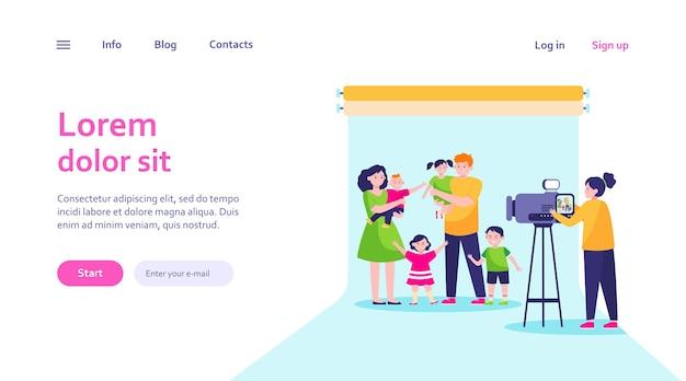 Kamerzysta kręci scenę rodzinną w studio. rodzice i dzieci pozują do szablonu sieci web aparatu.