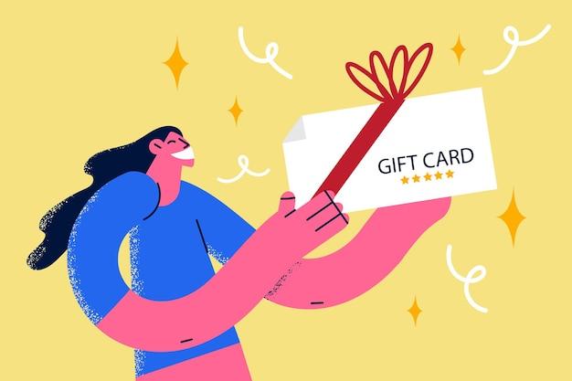 Karta podarunkowa i obecna koncepcja. młoda uśmiechnięta kobieta postać z kreskówki stojąca trzymająca kartę upominkową w świątecznym pudełku z ilustracją wektorową wstążką