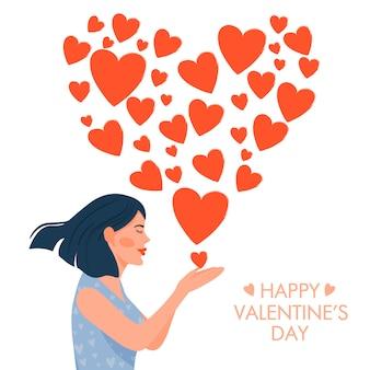 Karta walentynkowa. śliczna dziewczyna w miłości dmucha buziaka w kształcie serca.