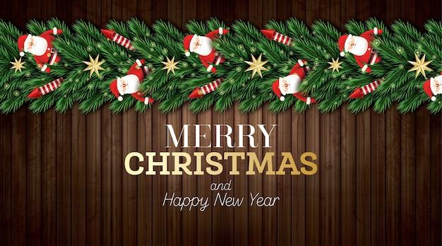 Kartka bożonarodzeniowa z gałązkami choinki, czerwonymi rakietami i mikołajem na podłoże drewniane.