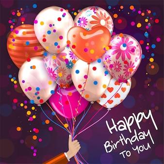 Kartka urodzinowa z ręką trzyma kolorowe balony
