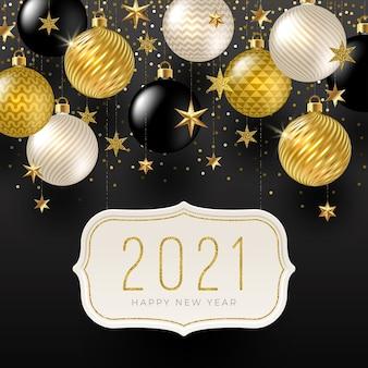 Kartkę z życzeniami noworocznymi ze złotymi gwiazdami, czarnymi, białymi i brokatowymi złotymi bombkami świątecznymi.
