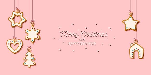 Kartkę z życzeniami świątecznymi. wiszące pierniki na różowym tle. świąteczne ciasteczka w kształcie domu i choinki, gwiazdy, płatka śniegu i serca. ilustracja wektorowa