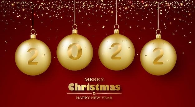 Kartkę z życzeniami wesołych świąt i szczęśliwego nowego roku 3d realistyczne złote bombki i konfetti