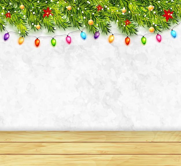 Kartkę z życzeniami z gałęzi choinki, girlandami i drewnianym blatem. wesołych świąt i szczęśliwego nowego roku pozdrowienia tło