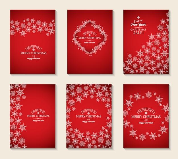 Kartki świąteczne i noworoczne z napisami okolicznościowymi i lekkimi eleganckimi płatkami śniegu na czerwono
