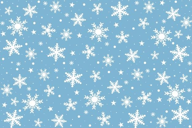 Kartki świąteczne z białymi płatkami śniegu na niebieskim tle.