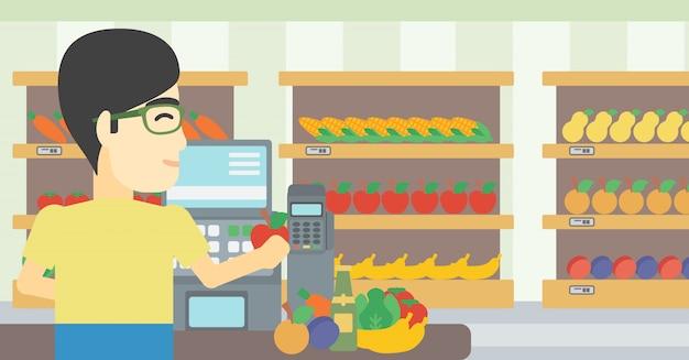 Kasjer stojący przy kasie w supermarkecie.