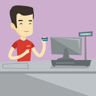 Kasjer trzyma kartę kredytową przy kasie.