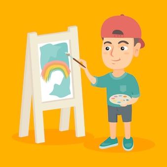 Kaukaski chłopiec artysta malujący obraz na płótnie.