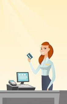Kaukaski kasjer trzyma kartę kredytową.