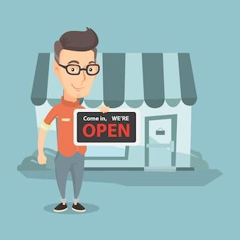 Kaukaski właściciel sklepu trzyma otwarty szyld.