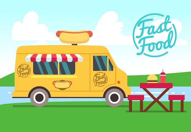 Kawiarnia na świeżym powietrzu z ciężarówką żywności i stoły. uliczne jedzenie