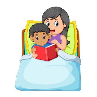 Kędzierzawy chłopiec idzie spać i czyta książkę z matką