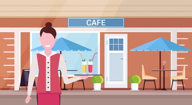 Kelnerka trzyma tacę z koktajlami profesjonalny pracownik serwujący napoje dla klientów nowoczesne lato kawiarnia sklep na zewnątrz ulica restauracja taras kobieta portret poziomy