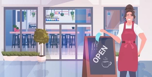 Kelnerka zdejmując maskę stojący w pobliżu otwartej planszy koronawirusa kwarantanny kończącej się koncepcji