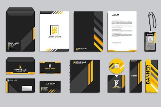 Klasyczny projekt szablonu tożsamości korporacyjnej z żółtymi i czarnymi kształtamielegancki zestaw profesjonalnych artykułów piśmienniczych dla firm