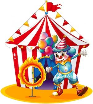 Klaun trzyma balony w pobliżu pierścienia ognia
