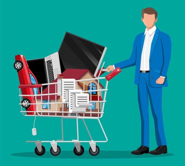 Klient z pełnym koszykiem supermarketu na białym tle na zielonym tle. metalowy wózek sklepowy na kółkach z zabudową domu, samochodem, laptopem, telewizorem i kwitem. ilustracja wektorowa w stylu płaski
