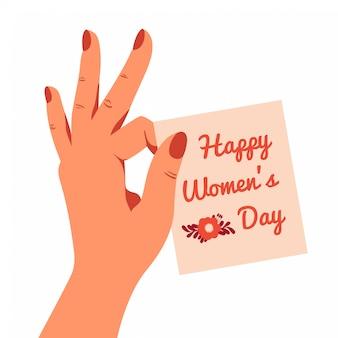 Kobieca ręka żartobliwie trzyma kartkę z życzeniami na międzynarodowy dzień kobiet 8 marca dwoma palcami.