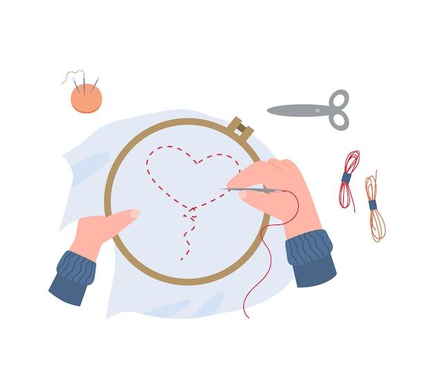 Kobiece ręce trzymają ramkę do haftowania i robią haft igłą z nicią